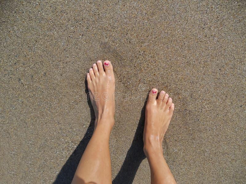Jonge vrouwenbenen die zich op zand op het strand bevinden royalty-vrije stock fotografie