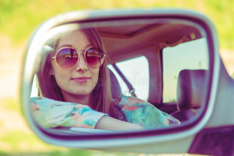 Jonge vrouwenbestuurder in de auto die aan de zijaanzichtspiegel kijken stock fotografie