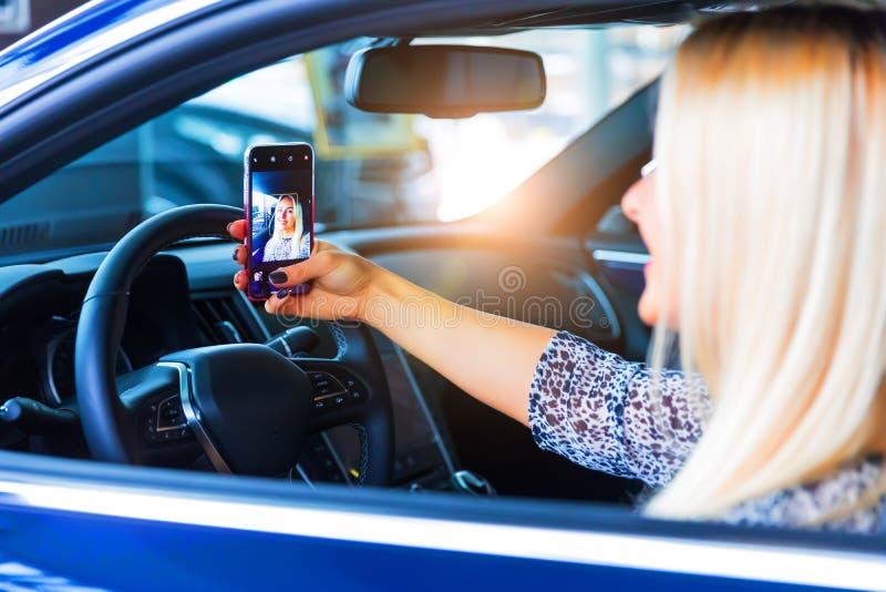 Jonge vrouwenbestuurder die een selfie in haar auto nemen royalty-vrije stock foto