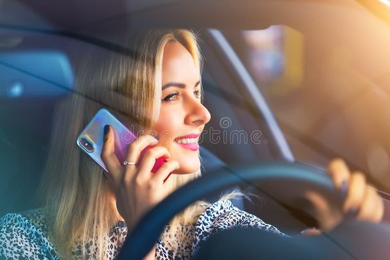 Jonge vrouwenbestuurder die telefonisch in de auto spreken stock foto's