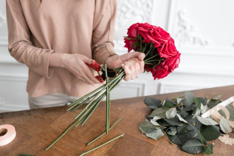 Jonge vrouwenbloemist die installaties in bloemwinkel schikken mensen, zaken, verkoop en floristry concept Boeket van rode rozen stock foto's