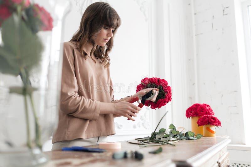 Jonge vrouwenbloemist die installaties in bloemwinkel schikken mensen, zaken, verkoop en floristry concept Boeket van rode rozen royalty-vrije stock afbeeldingen