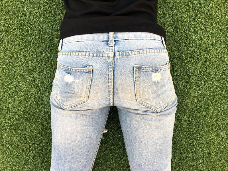 Jonge vrouwenbodem in lichtblauwe jeans voor groene grasachtergrond stock afbeeldingen