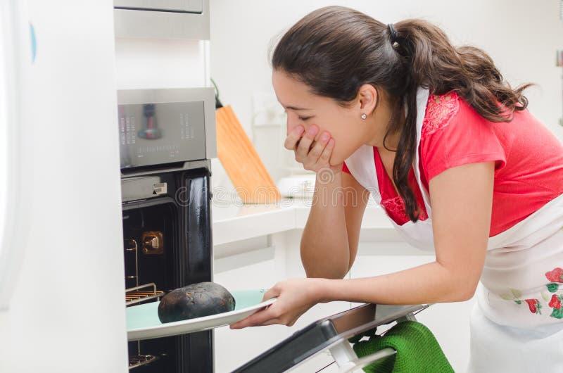 Jonge vrouwenchef-kok die oven met gefrustreerde gelaatsuitdrukking onderzoeken, die zwart gebrand brood op dienblad houden royalty-vrije stock fotografie