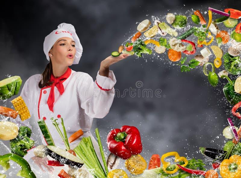 Jonge vrouwenchef-kok die verse groente blazen royalty-vrije stock afbeeldingen