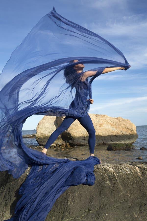 Jonge vrouwendanser die blauwe stof op een strand van Connecticut werpen stock foto