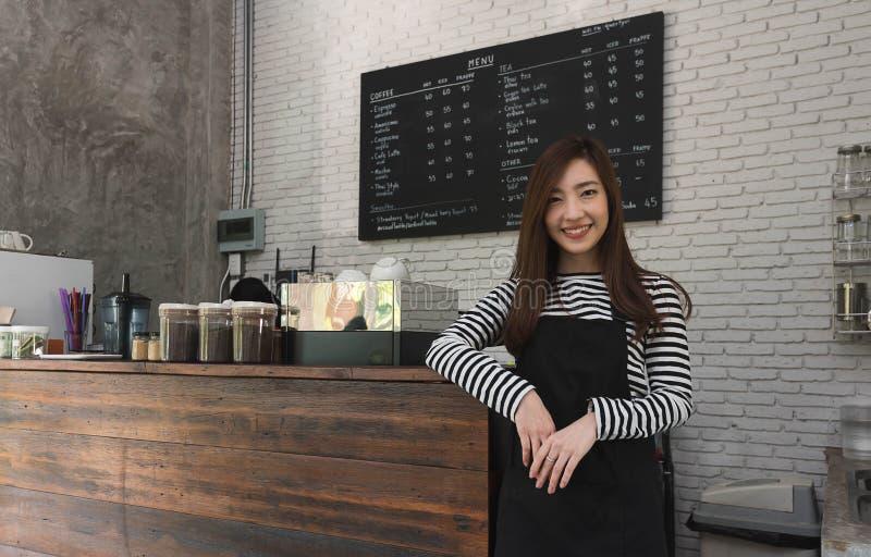 Jonge vrouweneigenaar van een koffietribune voor koffieteller, yo stock foto's