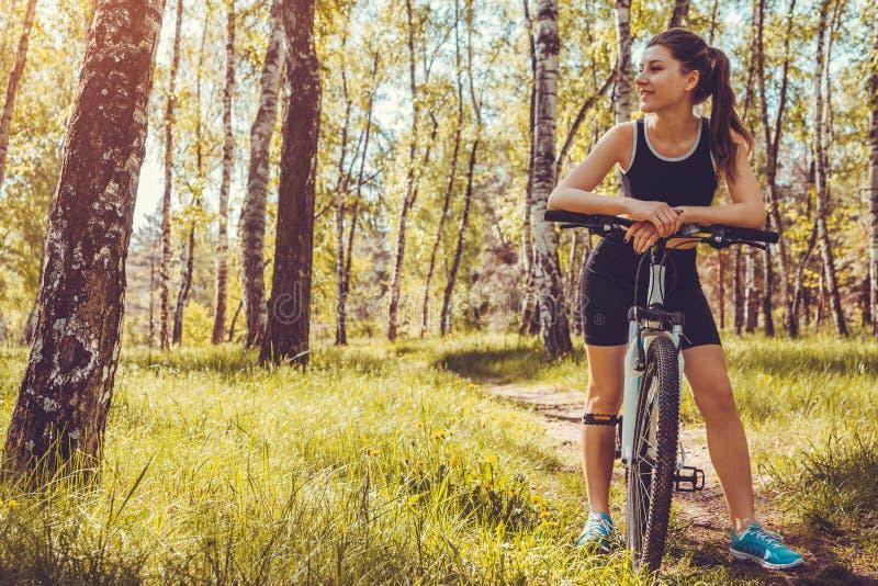 Jonge vrouwenfietser die een bergfiets in de lente bosmeisje berijden die rust hebben stock foto
