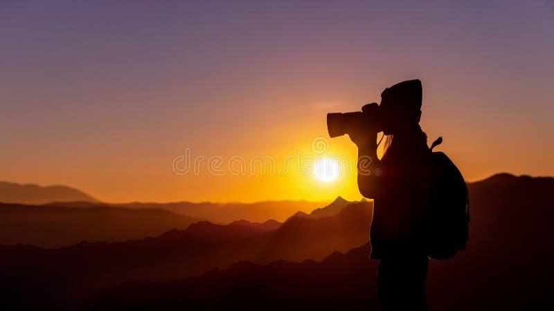 Jonge vrouwenfotograaf die foto met zonsondergang op berg natuurlijke achtergrond nemen stock foto
