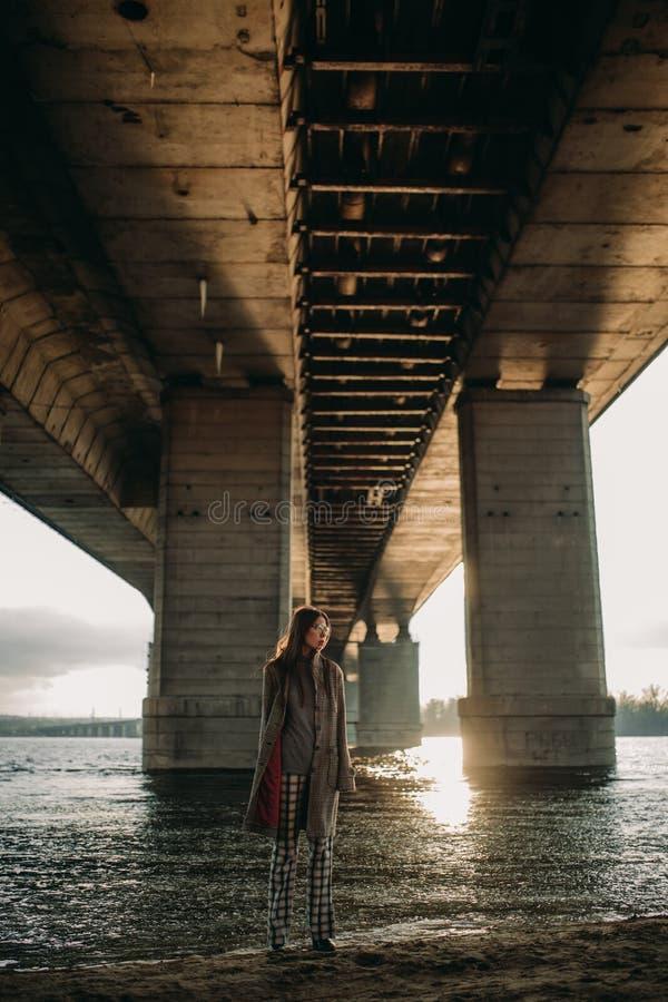 Jonge vrouwengangen op rivierbank bij zonsondergang onder brug royalty-vrije stock foto