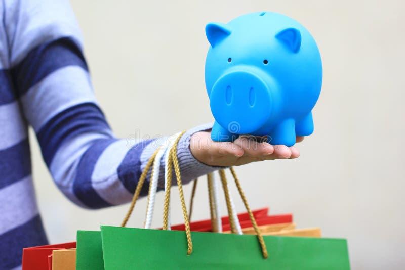 Jonge vrouwenhand die blauw spaarvarken en kleurrijke het winkelen zakken op witte achtergrond houden, die geld voor het winkelen stock fotografie