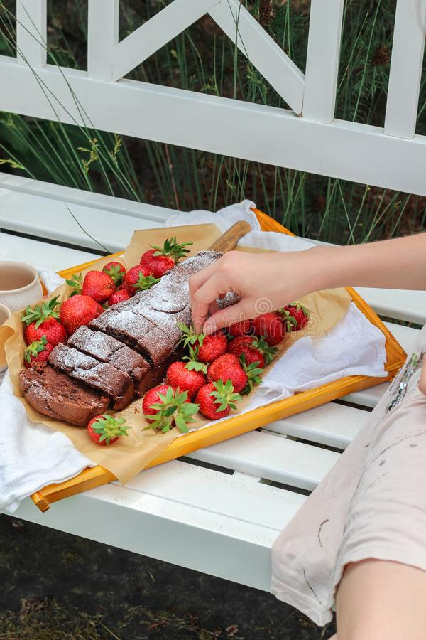 Jonge vrouwenhand die voor een dienblad met eigengemaakte cake en verse aardbeien bereiken stock afbeeldingen