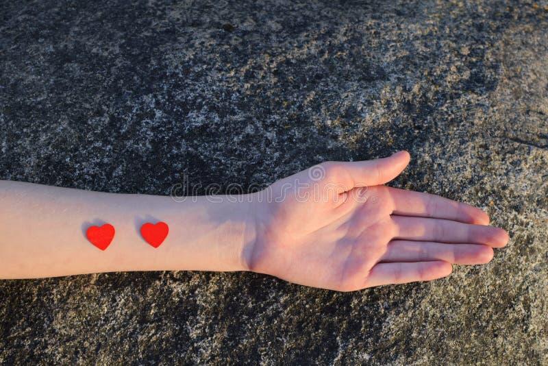 Jonge vrouwenhand met twee kleine rode harten royalty-vrije stock afbeeldingen