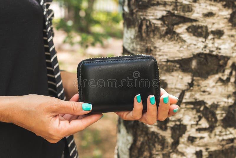 Jonge vrouwenhanden met de kleine houder van de portefeuillekaart op de aardachtergrond royalty-vrije stock foto's