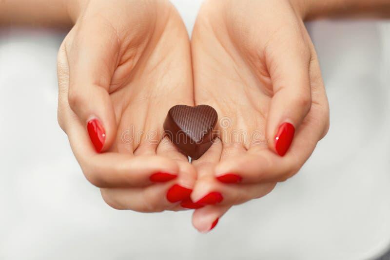 Jonge vrouwenhanden met donkere chocolade in een vorm van een hart Geniet van gezonde levensstijl Het suikergoed van de chocolade royalty-vrije stock afbeelding
