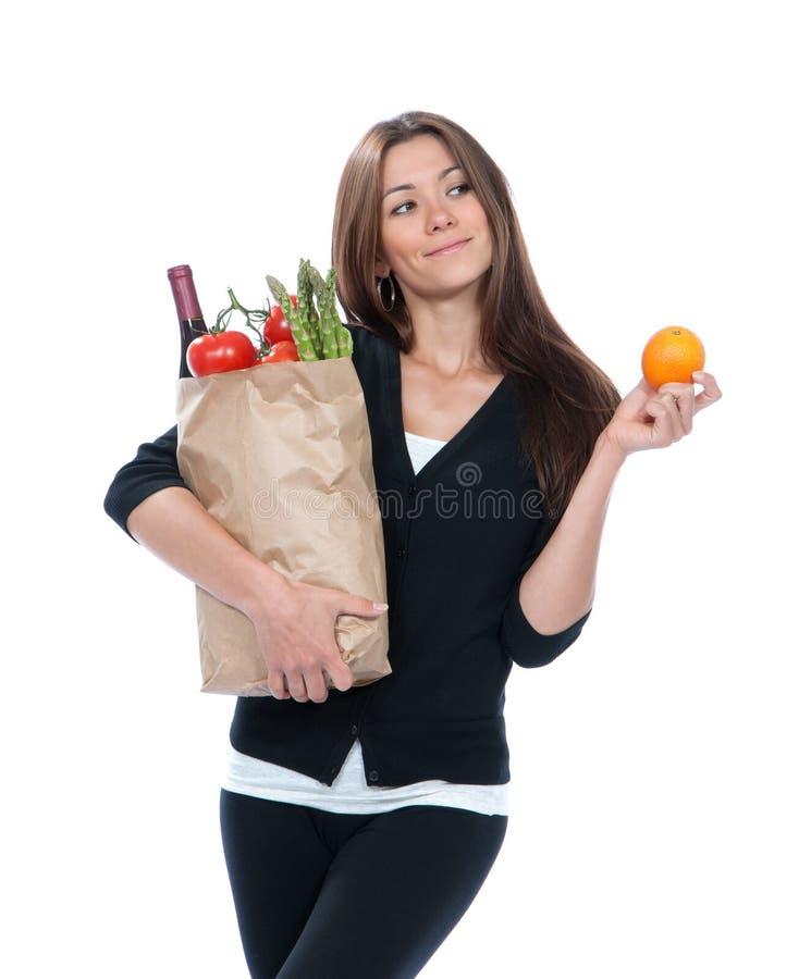 Jonge vrouwenholding het winkelen zak met kruidenierswinkelsgroenten stock afbeeldingen