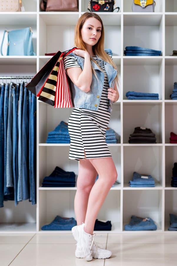 Jonge vrouwenholding het winkelen zakken en het kiezen van damesslijtage in kledingsopslag stock foto's