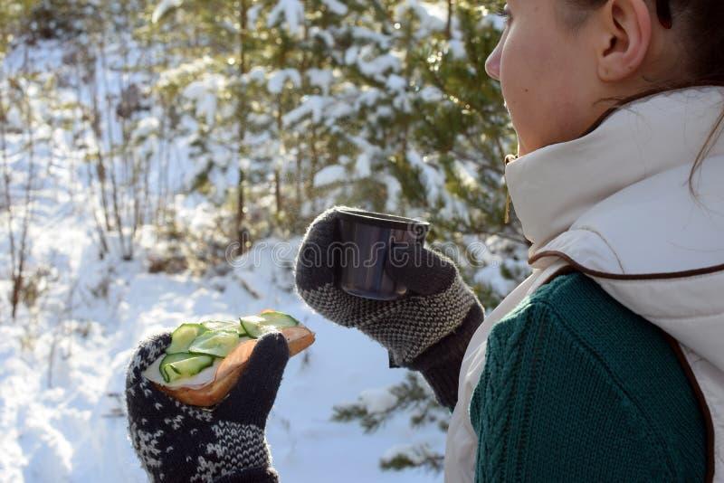 Jonge vrouwenholding sandwitch en koffiemok in de winterbos royalty-vrije stock afbeelding