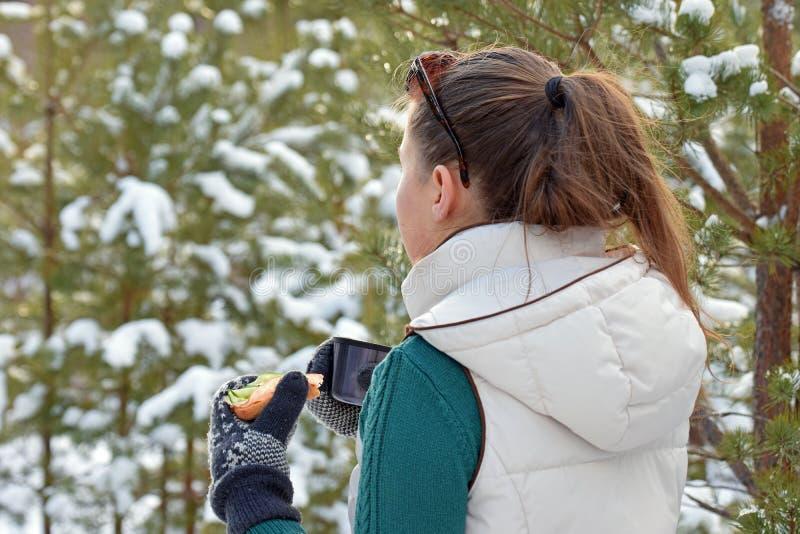 Jonge vrouwenholding sandwitch en koffiemok in de winterbos royalty-vrije stock afbeeldingen
