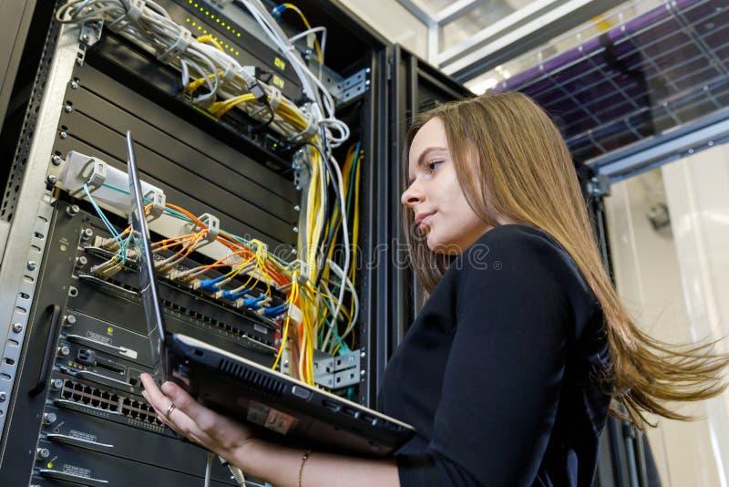 Jonge vrouweningenieur bij de netwerkapparatuur stock foto