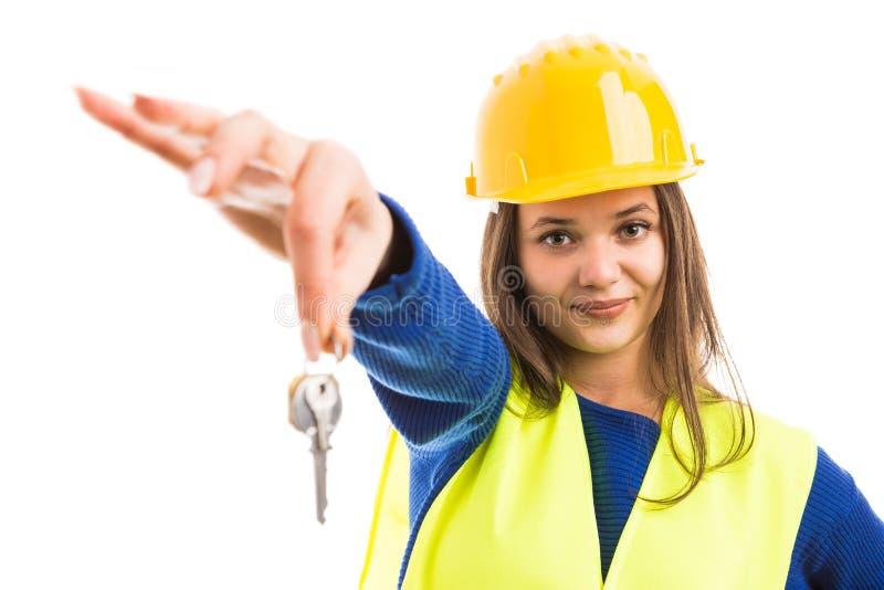 Jonge vrouweningenieur die huissleutels aanbieden royalty-vrije stock afbeelding