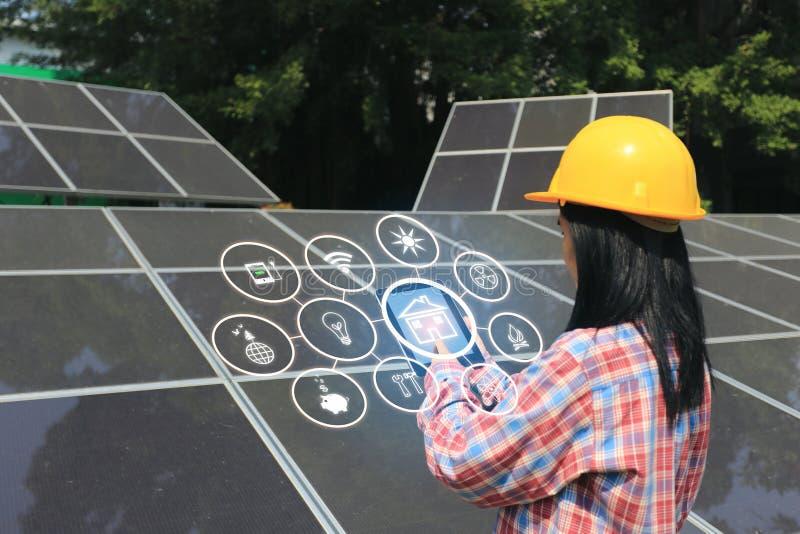 Jonge vrouweningenieur die zonnepaneel met hologram controleren bij zonneelektrische centrale stock afbeelding