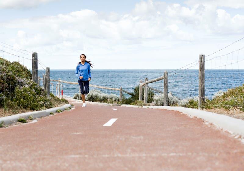 Jonge Vrouwenjogging bij de kust royalty-vrije stock fotografie