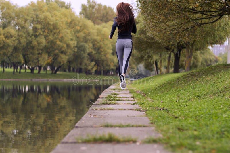 Jonge vrouwenjogging in de herfstaard op de bank van rivier De lopende achtermening van het Geschiktheidsmeisje stock afbeeldingen
