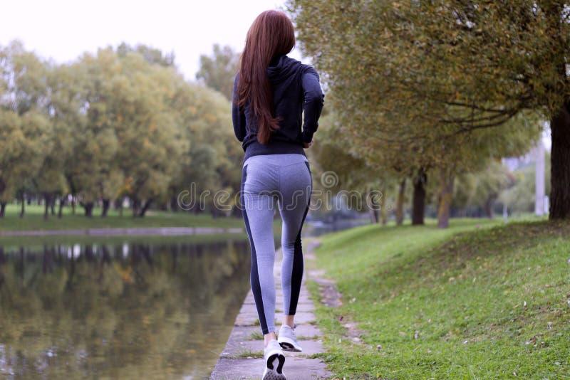 Jonge vrouwenjogging in de herfstaard op de bank van rivier De lopende achtermening van het Geschiktheidsmeisje royalty-vrije stock foto