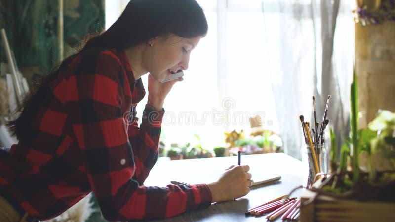 Jonge vrouwenkunstenaar die scetch op document notitieboekje met potlood en sprekende telefoon binnen schilderen royalty-vrije stock afbeelding