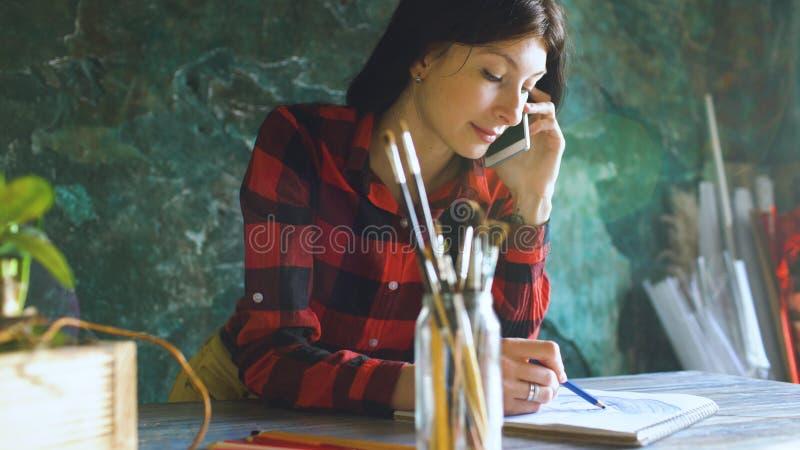 Jonge vrouwenkunstenaar die scetch op document notitieboekje met potlood en sprekende telefoon binnen schilderen royalty-vrije stock fotografie