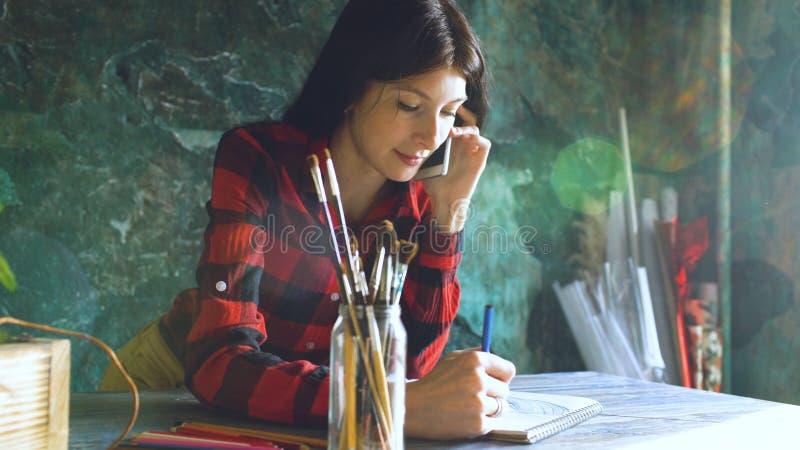 Jonge vrouwenkunstenaar die scetch op document notitieboekje met potlood en sprekende telefoon binnen schilderen royalty-vrije stock afbeeldingen