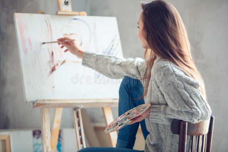Jonge vrouwenkunstenaar die thuis creatief portret in proces schilderen stock fotografie