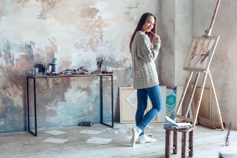 Jonge vrouwenkunstenaar die thuis creatieve bevindende het bijten borstel schilderen royalty-vrije stock foto