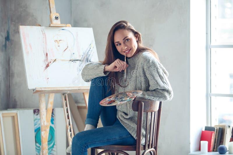 Jonge vrouwenkunstenaar die thuis creatieve het bijten verfborstel schilderen royalty-vrije stock foto
