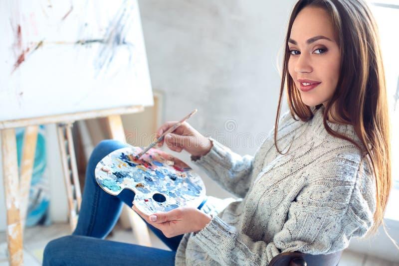 Jonge vrouwenkunstenaar die thuis creatieve het mengen zich kleuren schilderen stock foto