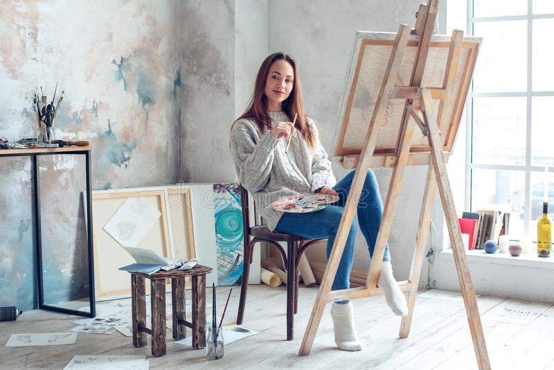 Jonge vrouwenkunstenaar die thuis creatieve holdingsborstel schilderen royalty-vrije stock afbeelding