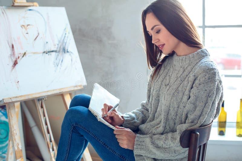Jonge vrouwenkunstenaar die thuis creatieve schets schilderen stock afbeelding
