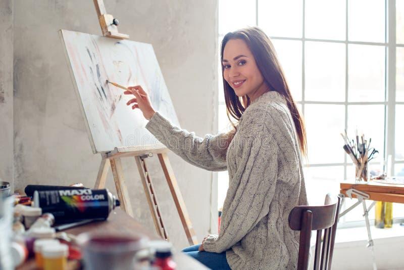 Jonge vrouwenkunstenaar die thuis creatieve zittingstekening schilderen stock afbeeldingen