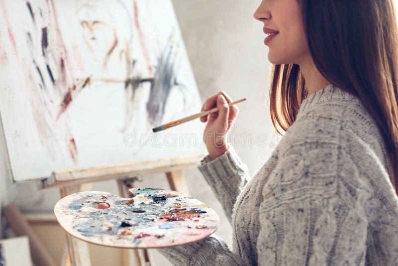 Jonge vrouwenkunstenaar die thuis het creatieve close-up van het holdingspalet schilderen stock foto