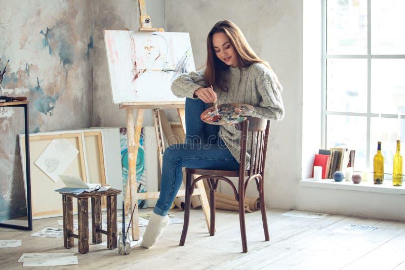 Jonge vrouwenkunstenaar die thuis het creatieve kijken onderaan het glimlachen schilderen stock fotografie