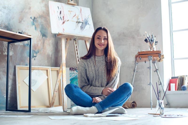 Jonge vrouwenkunstenaar die thuis het creatieve kijken schilderen camera het glimlachen royalty-vrije stock afbeeldingen