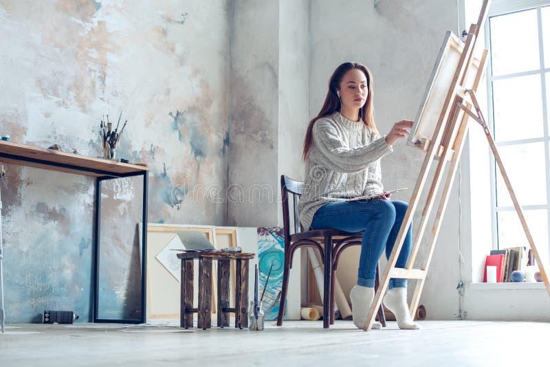 Jonge vrouwenkunstenaar die thuis het creatieve schilderen in proces schilderen stock fotografie