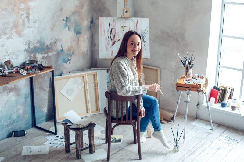 Jonge vrouwenkunstenaar die thuis het creatieve terugkeren schilderen royalty-vrije stock fotografie