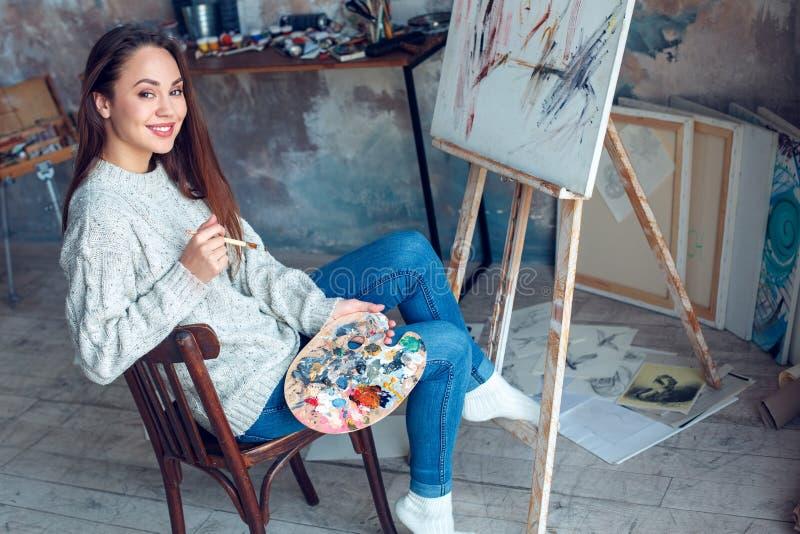 Jonge vrouwenkunstenaar die thuis het creatieve vrolijk glimlachen schilderen stock foto