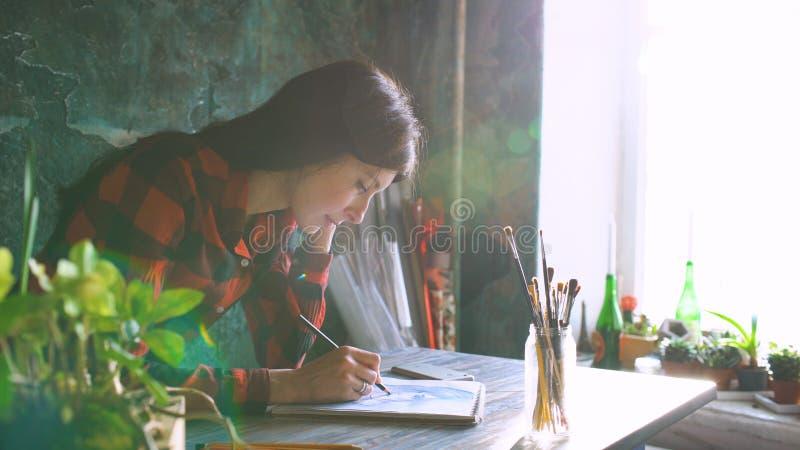 Jonge vrouwenkunstenaar het schilderen schets op document notitieboekje met potlood Heldere zongloed van venster royalty-vrije stock foto