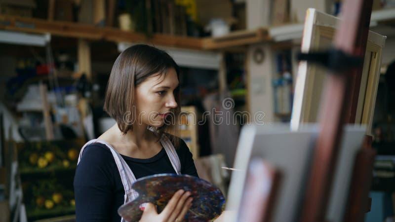 Jonge vrouwenkunstenaar in schort het schilderen beeld op canvas in kunststudio stock foto