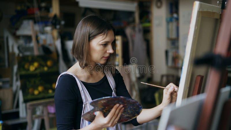 Jonge vrouwenkunstenaar in schort het schilderen beeld op canvas in kunststudio royalty-vrije stock afbeelding