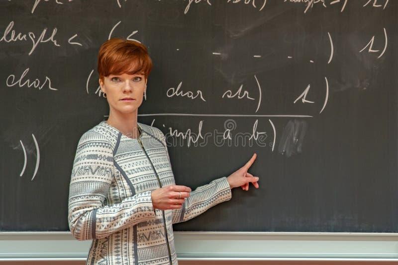 Jonge vrouwenleraar in universiteit Instructie in een universitair klaslokaal Bord door krijt wordt beschreven dat Projectie van stock fotografie