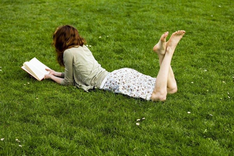 Jonge vrouwenlezing in het park stock fotografie